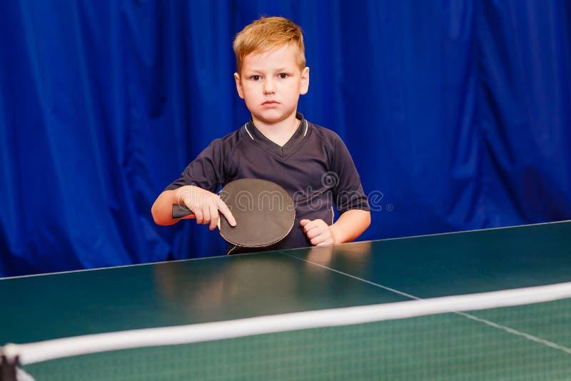 Sete anos de menino que guarda uma raquete preta para o tênis de mesa dentro imagem de stock