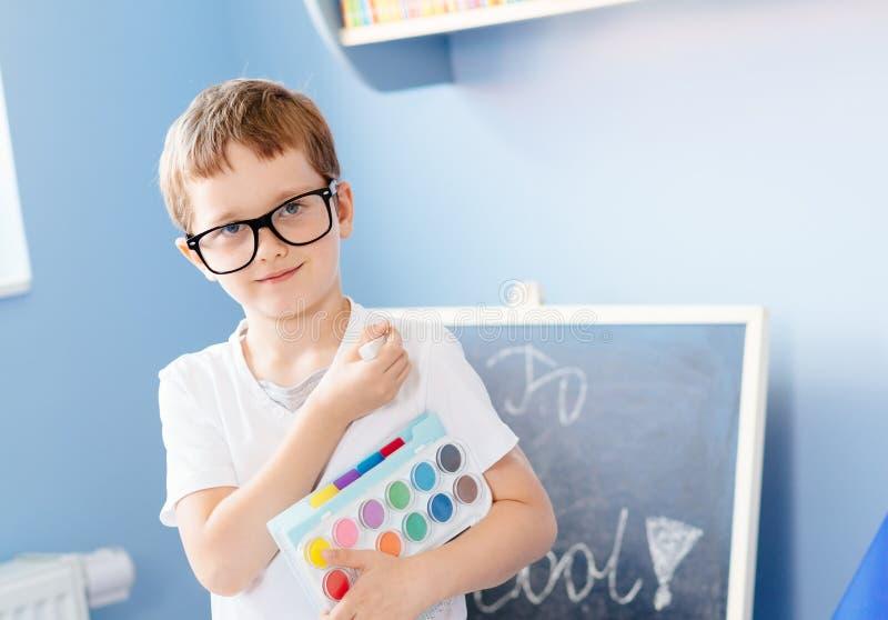 Sete anos felizes do menino idoso que guarda suas fontes de escola imagem de stock