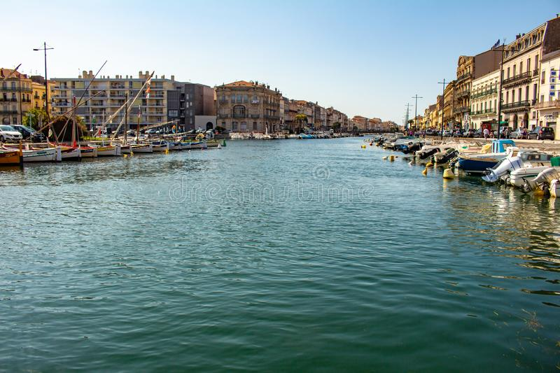 Sete, France May 20, 2018. Renaissance buildings next to the waters of the canals of the city populated by small boats stock photos