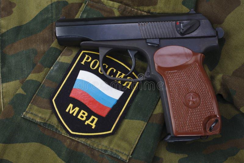 setembro 21, 2017 Crachá uniforme da polícia do russo com revólver Makarov no uniforme da camuflagem fotografia de stock royalty free