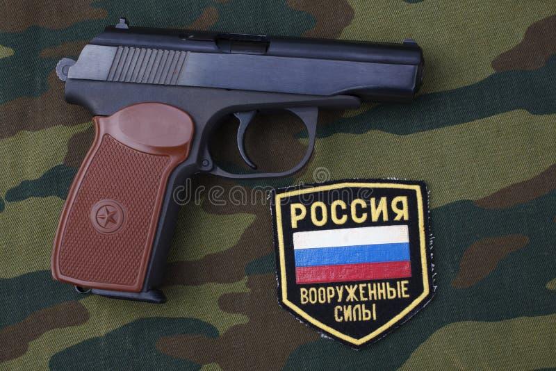 setembro 21, 2017 Crachá uniforme do exército do russo com revólver Makarov no uniforme da camuflagem imagens de stock