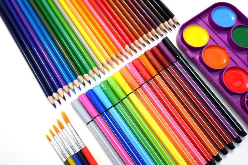 Sets of colored pencils, felt pen markers, watercolor paints and brushes stock image