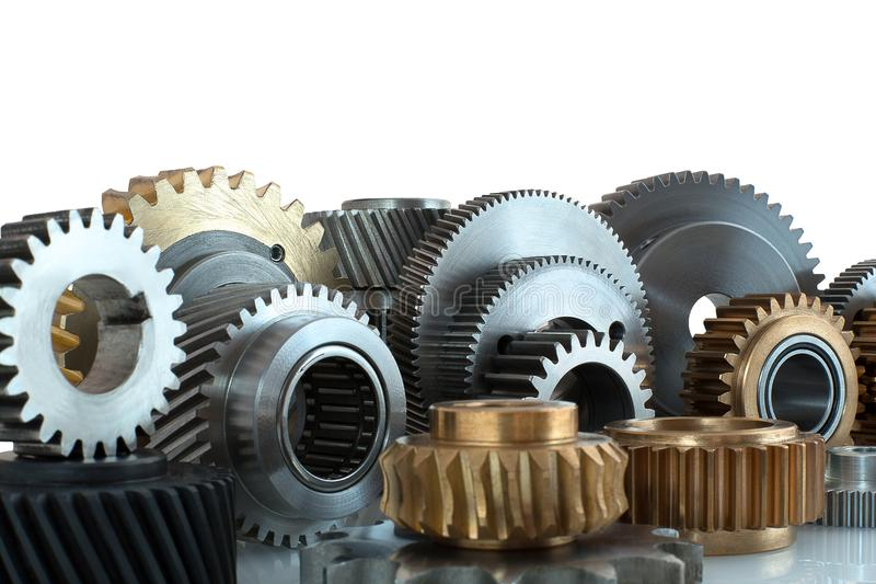 Sets of gears, cogwheels made of steel and brass isolated on white background with shadow reflection. Helical and spur gears,some. With bearing isolated on stock photo