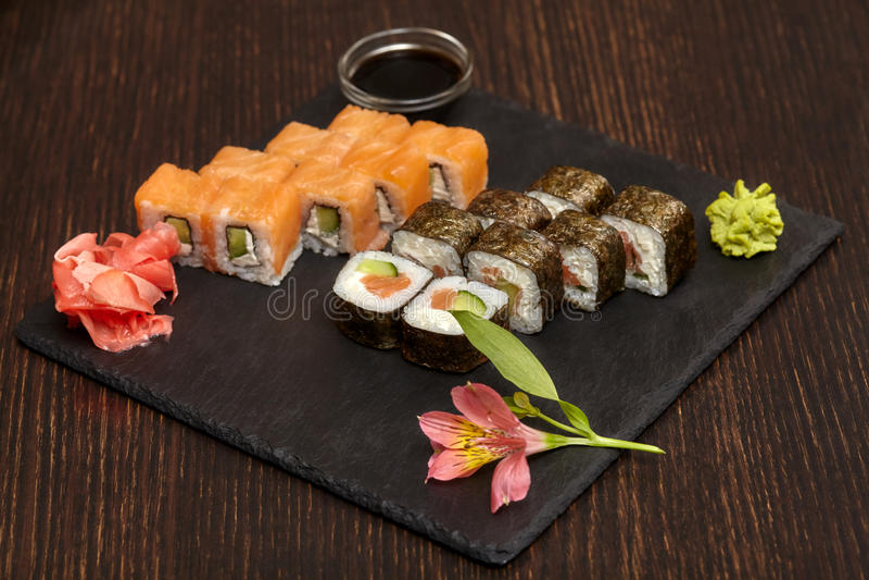 Sets of sushi rolls on black slate plate stock photo