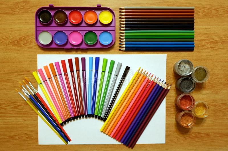Sets of watercolor paints, acrylic metallic paints and brushes, colored pencils and felt pens stock images