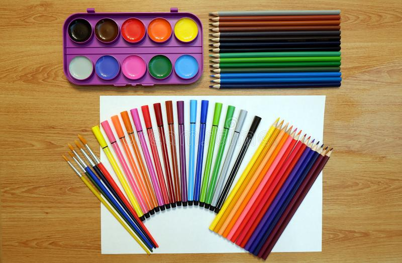 Sets of watercolor paints and brushes, colored pencils and felt pens, blank sheet of withe paper. On a wooden table vector illustration