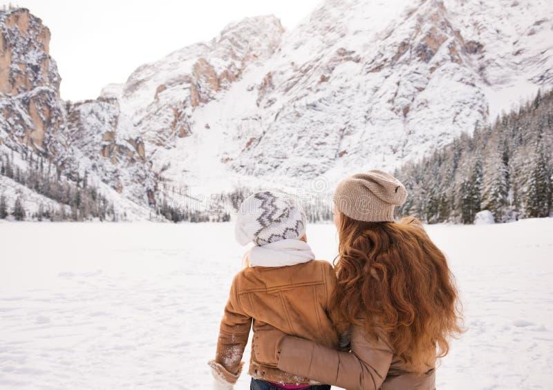 Sett bakifrån moder & barn som ser på snö-korkade berg arkivbild