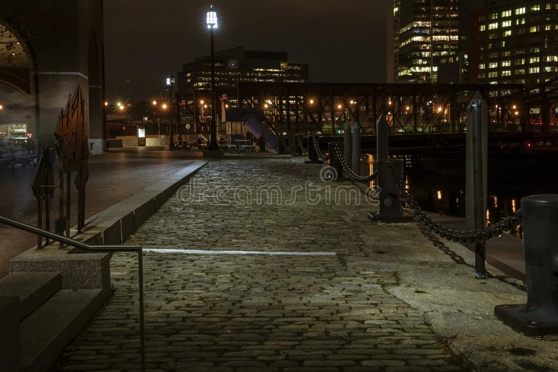 Sett stones glistening in pre-dawn illumination. South Boston, Massachusetts, USA - November 17, 2016: Walkway paved with sett stones along Fan Pier in South stock images