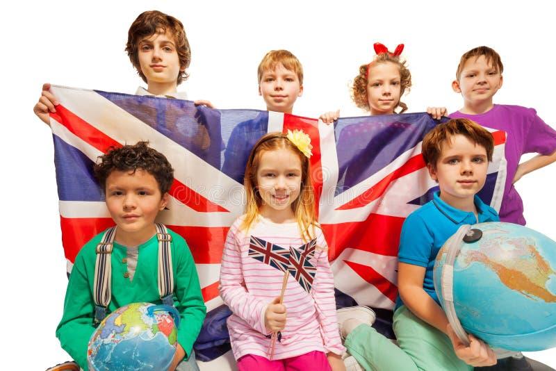 Sette bambini inglesi che studiano geografia con i globi fotografia stock