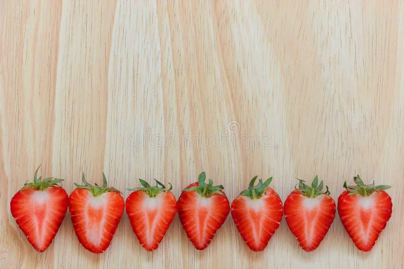 Sette pezzi di frutti freschi della fragola affettati a metà, su fondo di legno fotografia stock libera da diritti