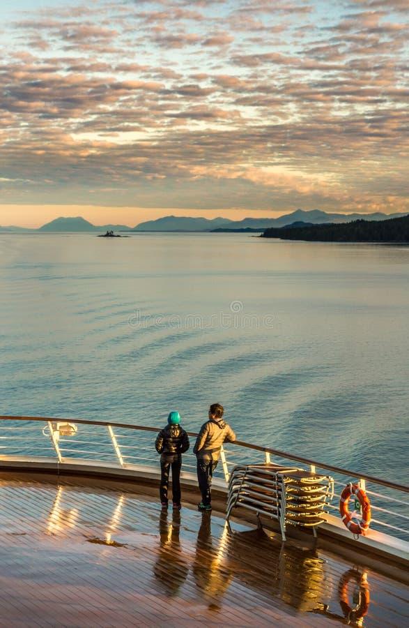 17 settembre 2018 - Clarence Strait, AK: Coppie calorosamente vestite, primo mattino sulla piattaforma di lido della nave da croc immagine stock libera da diritti