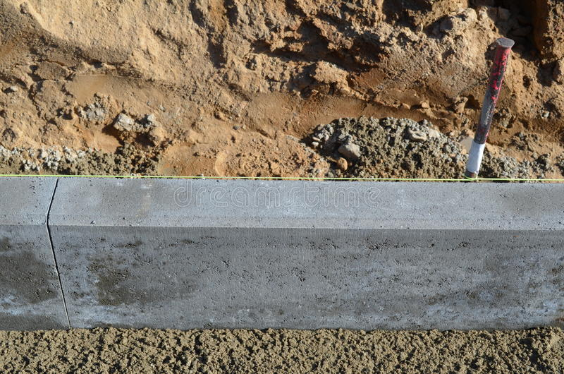 Setting a curbstone. Setting a concrete cornerstone in fresh cement royalty free stock photos