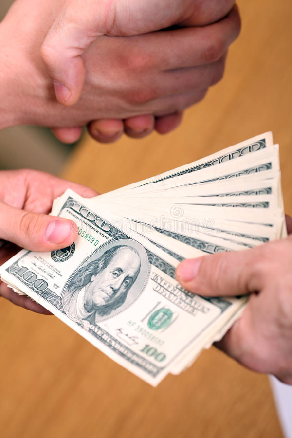 Setting a deal. Businessman setting a deal passing money and shaking hands royalty free stock image