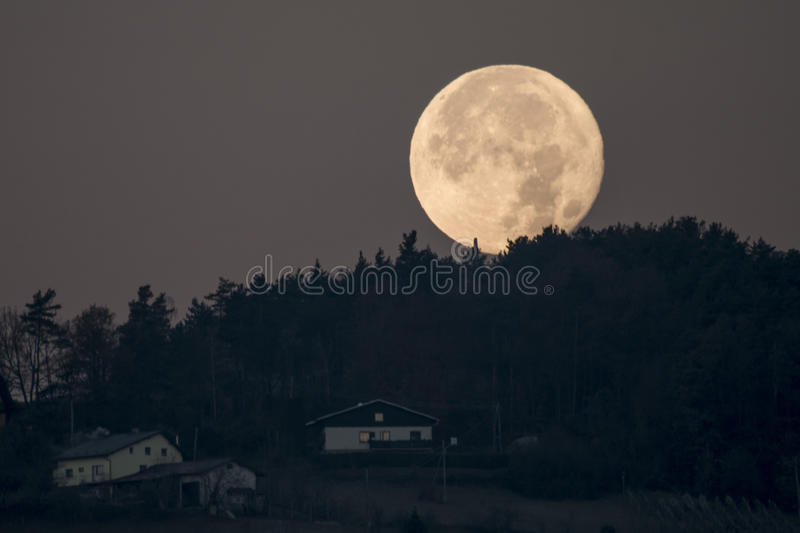 Setting full moon behind hill, forest and houses seen on hill royalty free stock photography