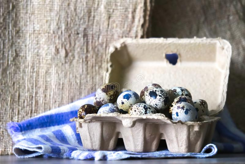 A large carton of several quail eggs, on a cloth background. royalty free stock image
