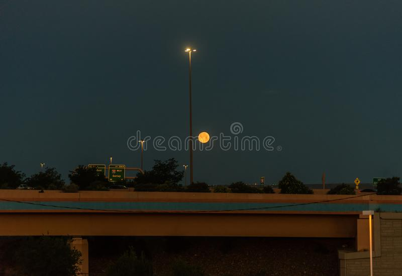 Setting moon in the pre-dawn hour in Albuquerque, New Mexico. Setting moon over a freeway in the pre-dawn hour in Albuquerque, New Mexico stock photography