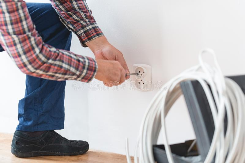 Setting the outlet. Close-up of electrician setting the outlet in the room stock image