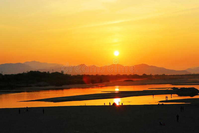 The setting sun. On April 30, 2017, location: China,When burn the red sunset glow up half the sky, people on the beach in collecting shells, some in royalty free stock photography