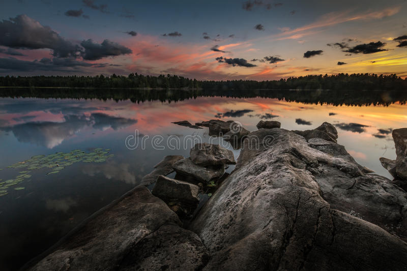 A setting sun with clouds reflected on a smooth lake. stock photo