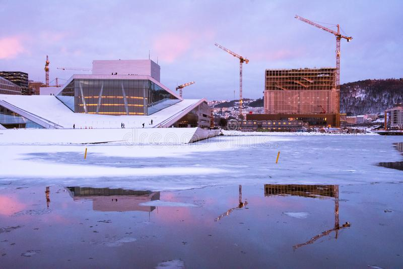 Oslo Opera House at the Fjord in winter, Norway. The setting sun colors the Opera House of Oslo purple with reflections in the water and ice surface. Building stock photos
