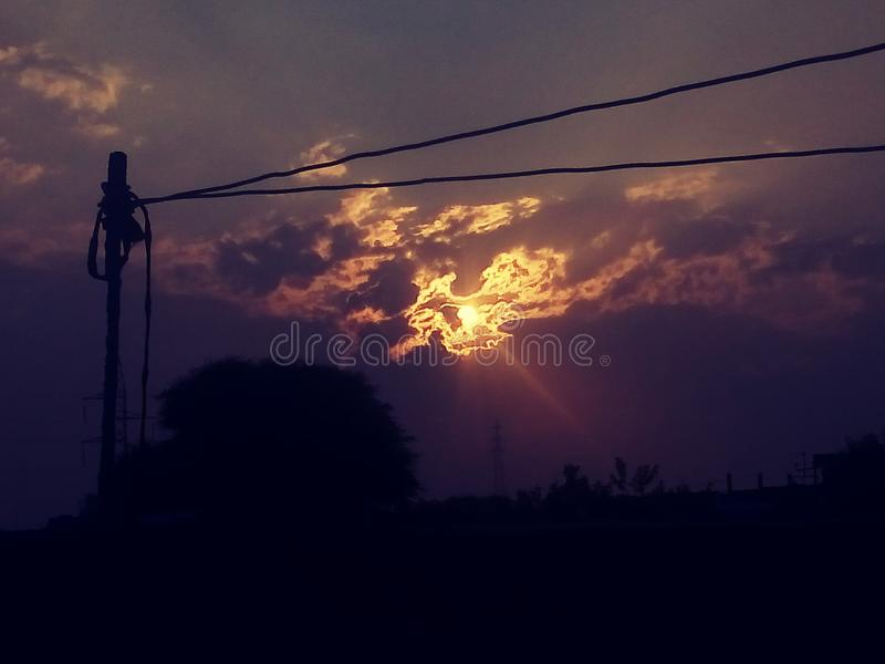 The setting sun, evening view. Evening scene, the setting sun Adorable scenes of red, yellow and purple color The setting sun with poles and wires royalty free stock photography