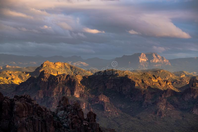 The setting sun illuminates the rugged desert mountain landscape of the Superstition Mountains, Arizona royalty free stock image