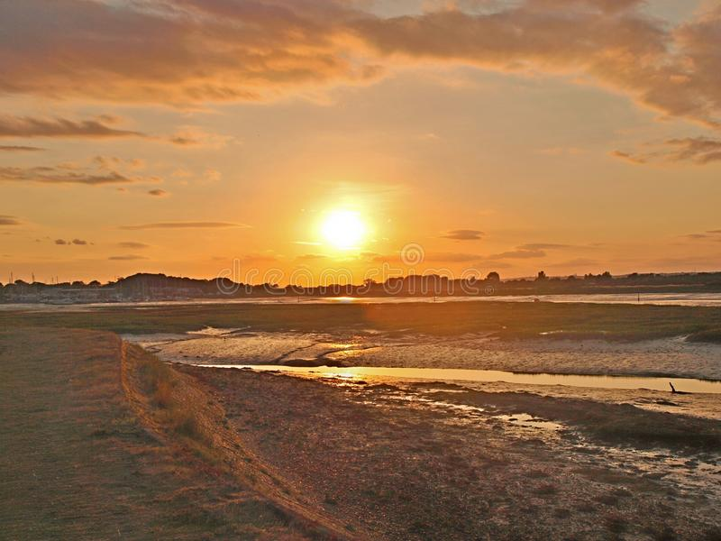 Sunset across the bay at low tide. Setting sun like a giant orange in the evening sky casting shadows and reflections across mudflats at low tide royalty free stock photo