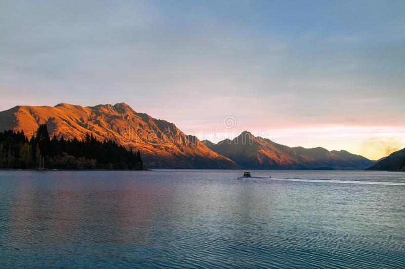 Romantic sunset at Lake Wakatipu, golden sun reflection on Walter and Cecil Peak, Queenstown New Zealand royalty free stock images