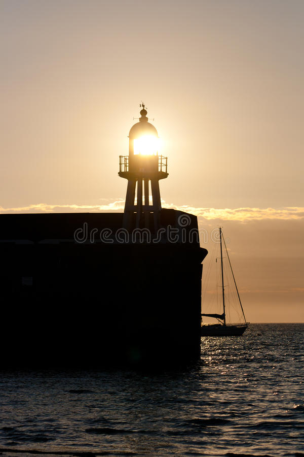 The setting sun shines through a lighthouse on a Port Erin Harbour. Port Erin harbout, known as Raglan Pier at sunset with the sun shining through the lighthouse stock image