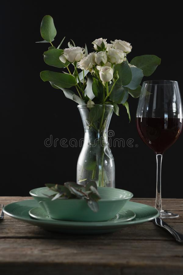 Setting a table for a dinner party with wine glass and flower vase. On table royalty free stock images