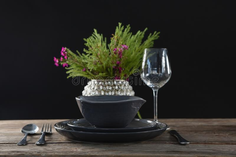 Setting a table for a dinner party with wine glass and flower vase. On table stock photography