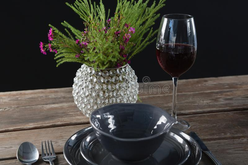 Setting a table for a dinner party with wine glass and flower vase. On table royalty free stock image