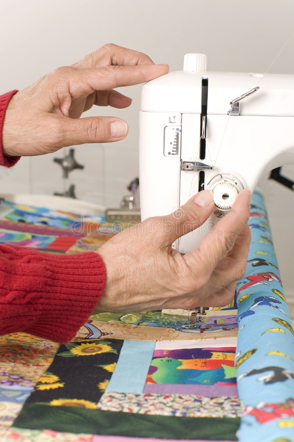 Setting tension on quilting machine. A woman quilter is setting the tension on the bobbin during the machine quilting process stock photography