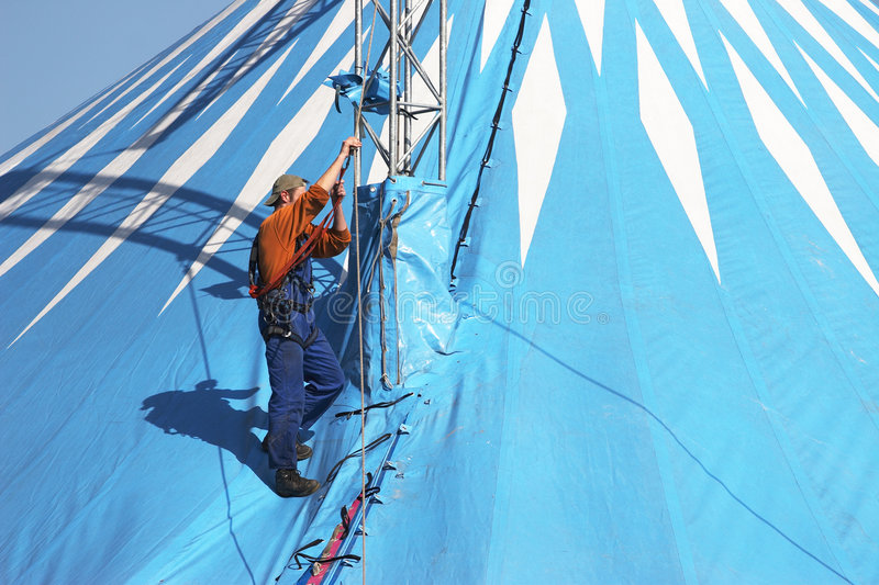 Setting up the tent for a circus. Worker setting up the tent for a circus royalty free stock image