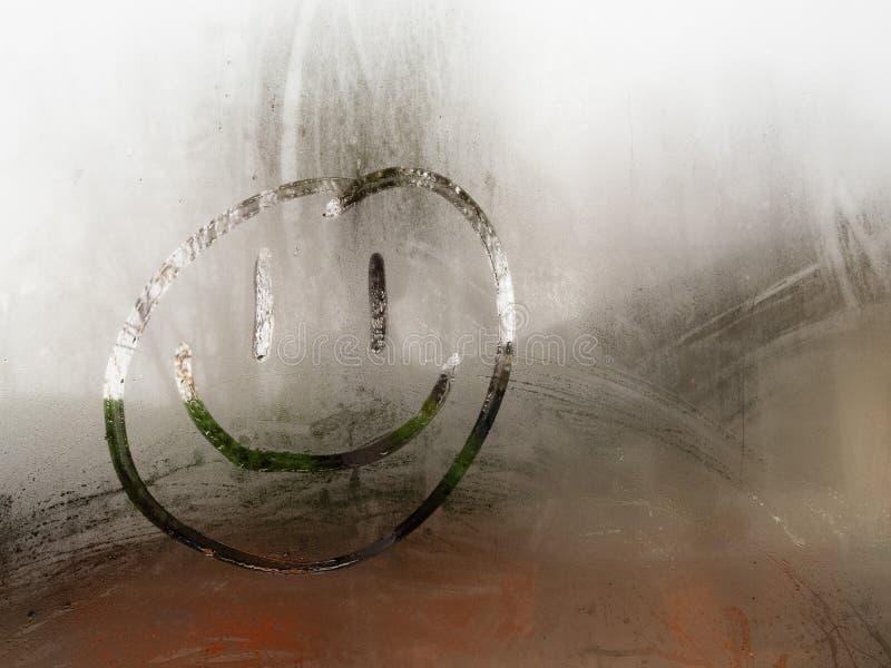 Setzen das glückliche smileygesicht der Karikatur, das auf ein Kondensation bedecktes Fenster gezeichnet wird tagsüber Zeit fest stockfotografie