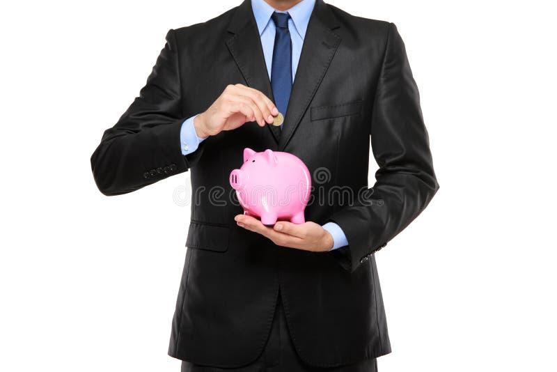 Setzen einer Münze in eine piggy Querneigung lizenzfreie stockbilder