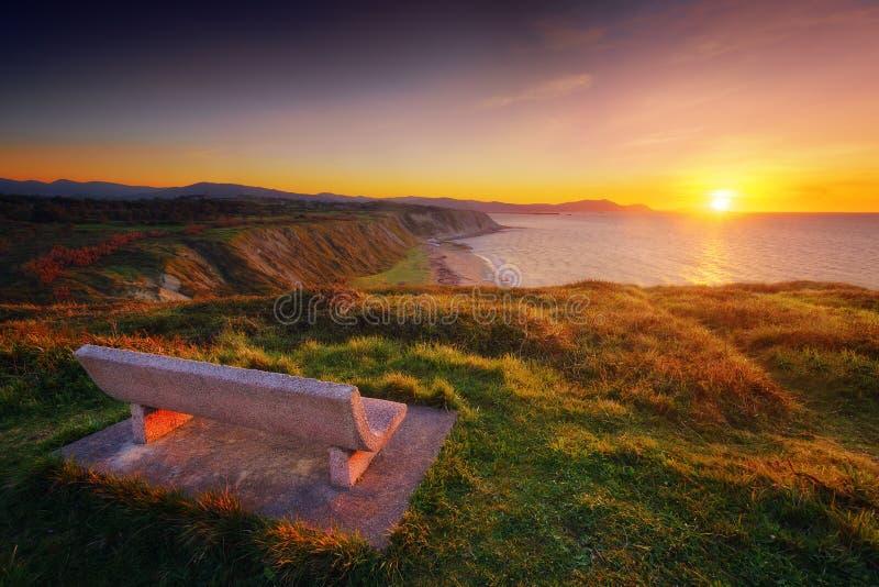 Setzen Sie bei Sonnenuntergang mit Ansicht von Azkorri-Strand in Getxo auf die Bank stockbild