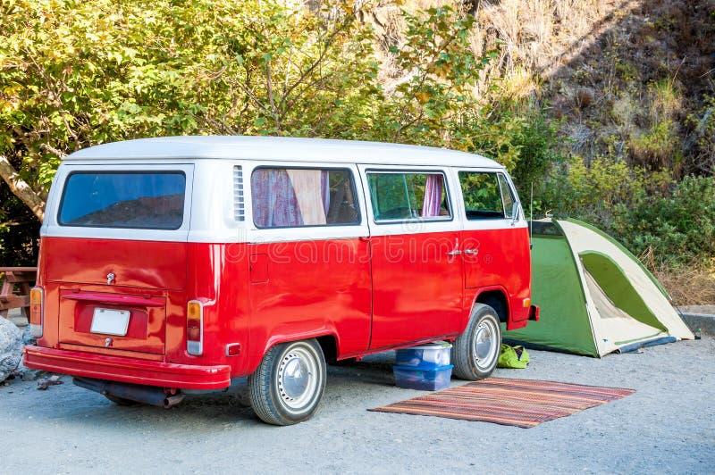 Setzen Sie Campingplatz mit rotem Hippiekleinbus, grünem Zelt und rustikaler Wolldecke auf den Strand lizenzfreie stockfotografie