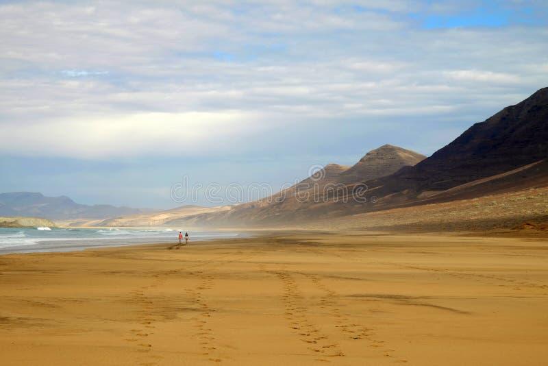 Setzen Sie Cofete und ein Paar, das entlang es auf Fuerteventura, Spanien geht auf den Strand lizenzfreie stockbilder