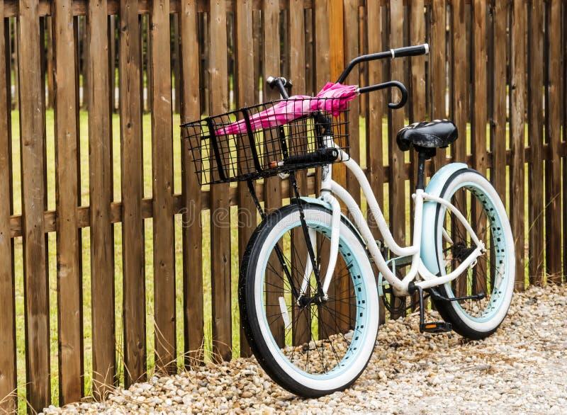 Setzen Sie das Fahrrad auf den Strand, das gegen einen Zaun mit Regenschirmen in seinem Korb geparkt wird lizenzfreies stockfoto