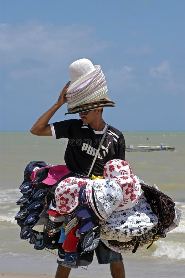 Setzen Sie den Verkäufer auf den Strand, der Hüte und Kappen, Brasilien verkauft lizenzfreies stockfoto