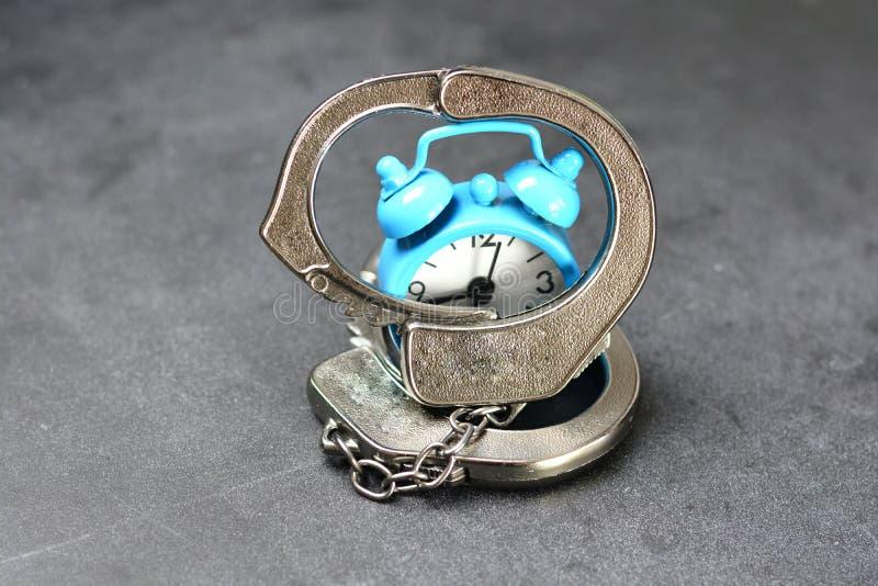 Setzen Sie des Sklaven oder Zeit Gefangenen des Zeitkonzeptes mit den metallischen Handschellen und Wecker auf dunklem Hintergrun stockfoto