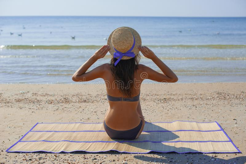 Setzen Sie die Feiertagsfrau auf den strand, welche die Sommersonne genie?t, die im Sand sitzt, der Exemplarplatz gl?cklich betra lizenzfreie stockfotografie