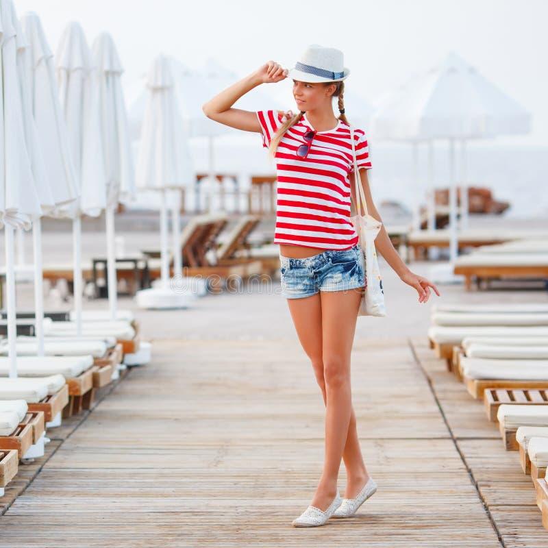 Setzen Sie die Frau auf den Strand, die glücklich ist und setzen Sie den Hut auf den Strand, der Sommerspaß während der Reisefeie lizenzfreies stockbild