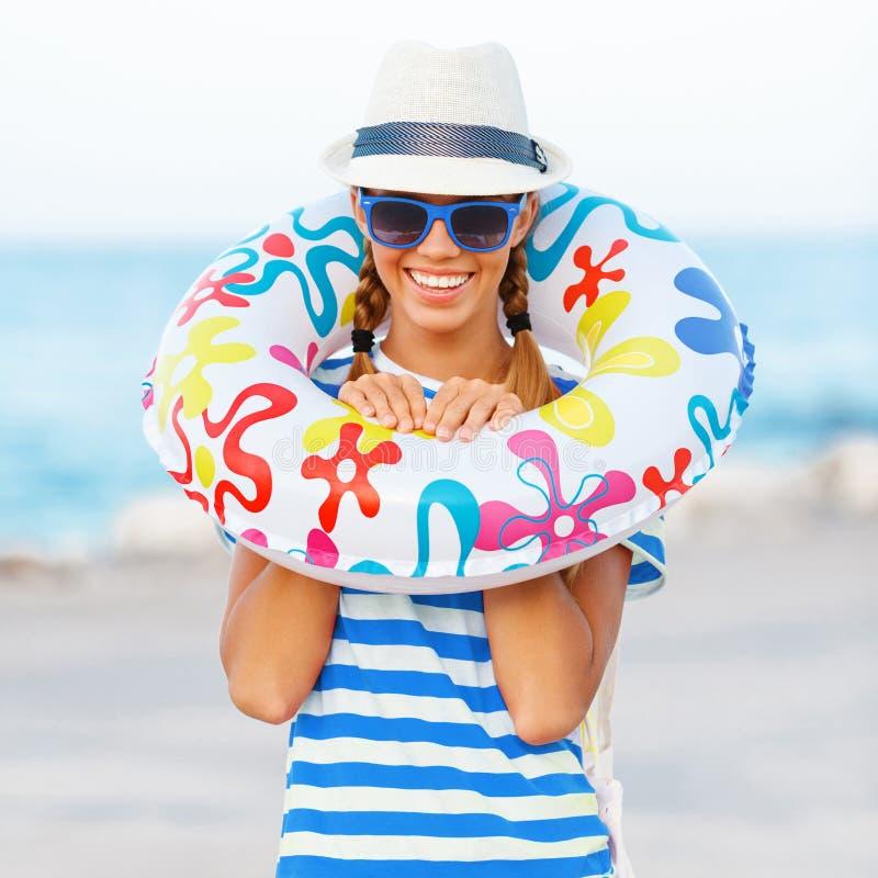 Setzen Sie die Frau auf den Strand, die glücklich sind und bunte tragende Sonnenbrille und den Strandhut, der Sommerspaß während  lizenzfreie stockfotografie