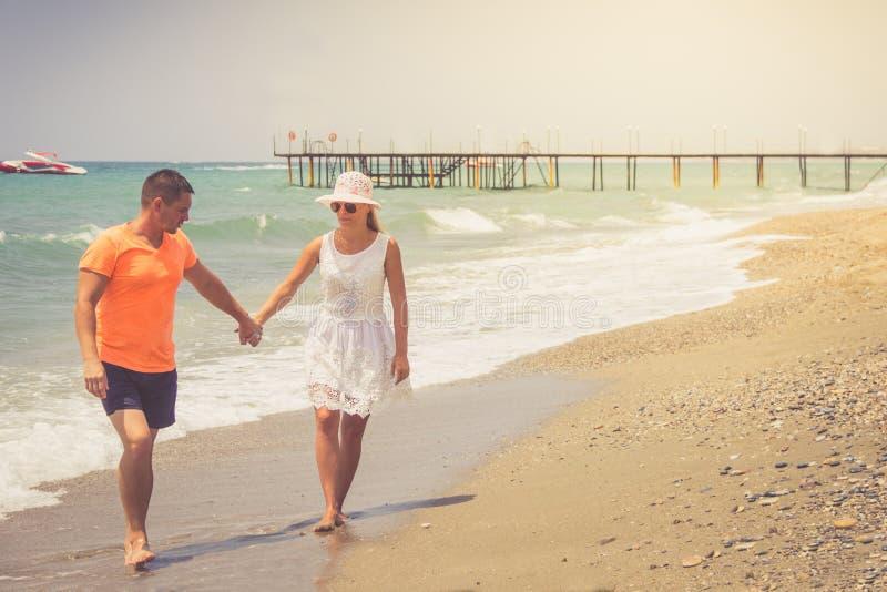 Setzen Sie die Paare auf den Strand, die an den romantischen Reiseflitterwochenferien-Sommerferien Romanze gehen Junge glückliche stockbild