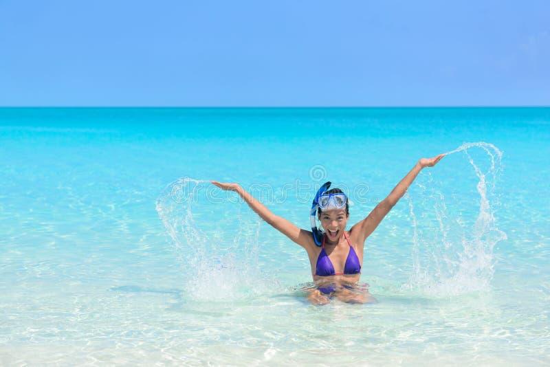 Setzen Sie die Spaßfeiertags-Frauenschwimmen auf den strand, die im Wasser spielt stockbild