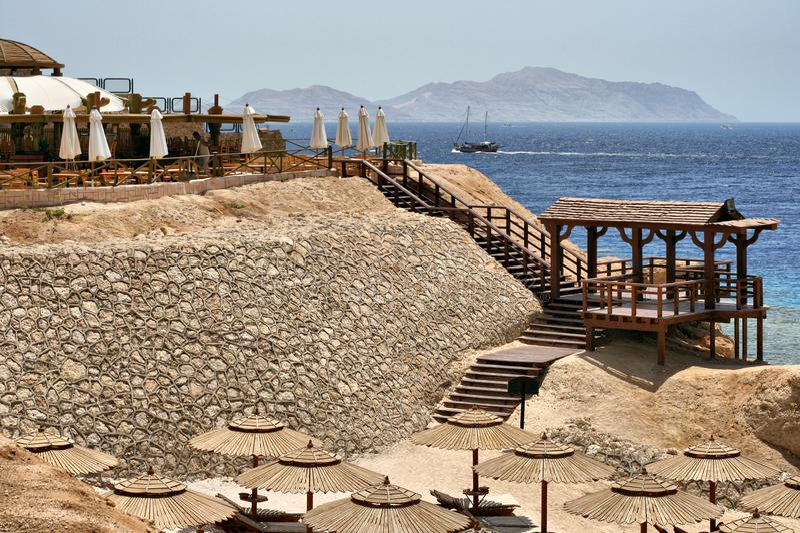 Setzen Sie durch das Meer mit Sonnenruhesesseln und -pier auf den Strand stockbilder