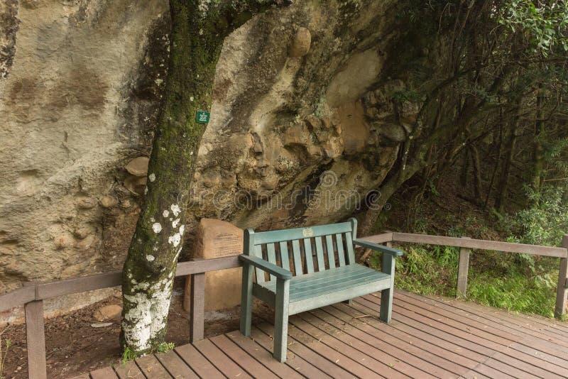 Setzen Sie am Felsenkunststandort nahe den Kaskaden auf die Bank lizenzfreie stockfotografie