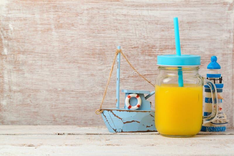 Setzen Sie Ferienkonzept mit Orangensaft und Seedekorationen auf den Strand lizenzfreies stockfoto